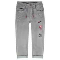 Jeans effet used avec taches printées et badges patchés